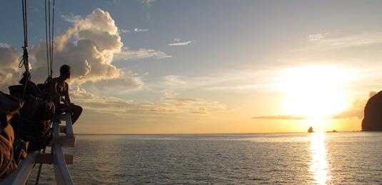 Ville sitter i fören och tittar när solen går ner över horisonten